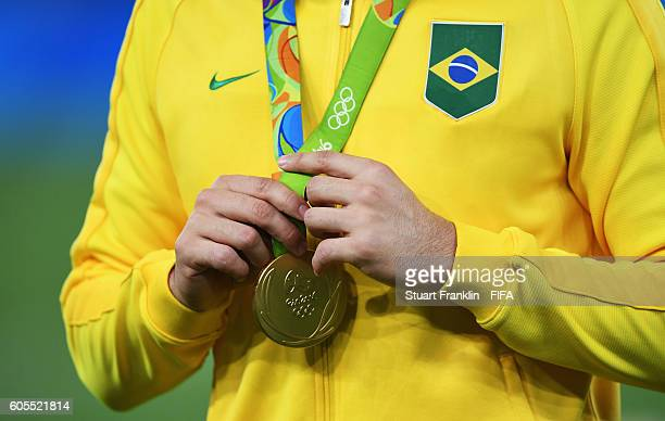 The Olympic gold medal hangs around the neck of player of Brazil after the Olympic Men's Final Football match between Brazil and Germany at Maracana...