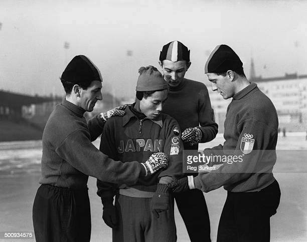 The Olympic Italian speed skating team take a keen interest in the badges worn by Japanese speed skater Kiyotaka Takabayashi during practice sessions...