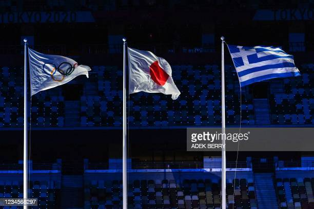 The Olympic, Japanese and Greek flags are pictured during the closing ceremony of the Tokyo 2020 Olympic Games, at the Olympic Stadium, in Tokyo, on...