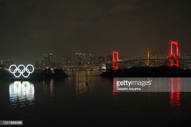 The Olympic rings and the Rainbow Bridge are illuminated on June 02, 2020 in Tokyo, Japan. The Rainbow Bridge, normally lit in rainbow colors is lit...