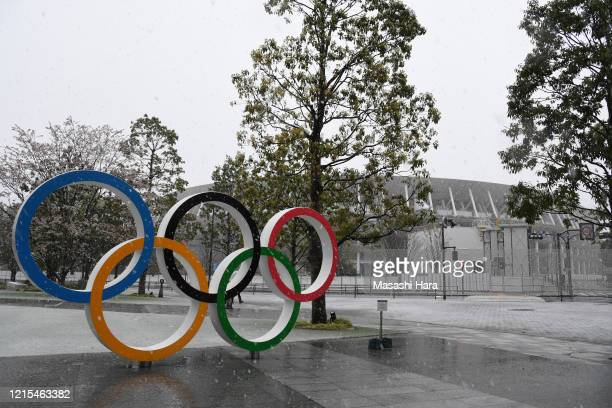 The Olympic Rings are displayed in front of the National Stadium while snow falls on March 29 2020 in Tokyo Japan A low pressure system brings...