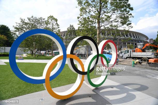 The Olympic Rings are displayed in front of the new national stadiumm which construction continues on the day marking the one year to go to the Tokyo...