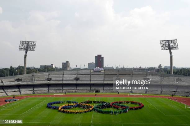 The Olympic rings are formed on the field by performers during the ceremony to mark the 50th anniversary of Mexico's 1968 Summer Olympics at the...