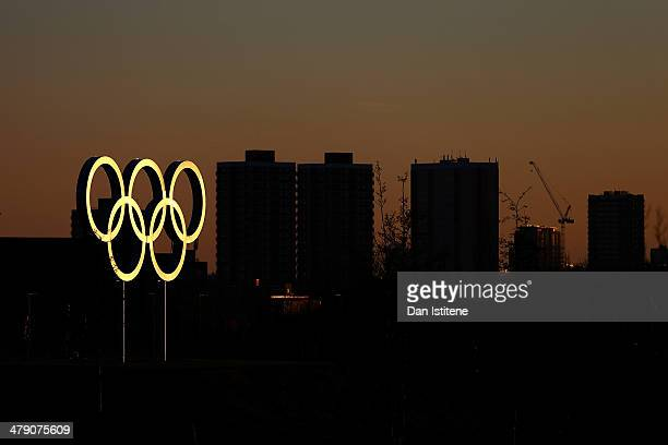 The Olympic rings are illuminated during a sunset backdropped by apartment blocks near Stratford inside the Olympic Park before the Revolution 5 at...