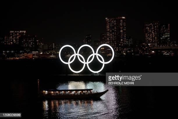 The Olympic rings are seen at Tokyo's Odaiba district on March 23, 2020. - World Athletics chief Sebastian Coe has called for the Tokyo Olympics to...