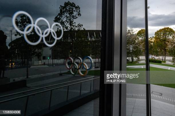The Olympic rings are seen reflected in the window of the closed Japan Olympic Museum in Tokyo on March 27 three days after the historic decision to...