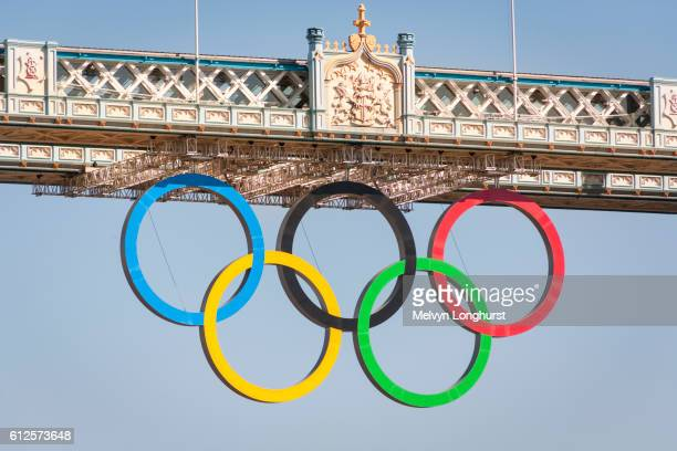the olympic rings, celebrating the 2012 olympic games, suspended from tower bridge, london, england - the olympic games stock pictures, royalty-free photos & images