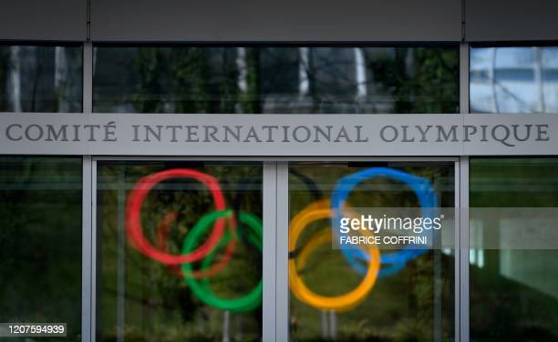 The Olympic Rings logo are reflected in the windows of the headquarters of the International Olympic Committee in Lausanne on March 18 as doubts...