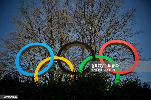 The Olympic Rings logo is pictured in front of the headquarters of the International Olympic Committee in Lausanne on March 18 as doubts increase...