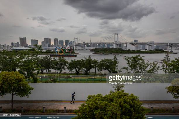 The Olympic Rings loom in the background as a man runs near the Odaiba Marine Park Olympic venue on June 03, 2021 in Tokyo, Japan. Tokyo 2020...