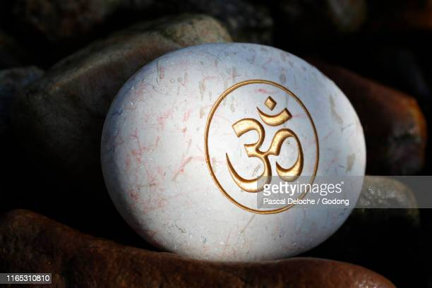 the om or aum symbol of hinduism and buddhism painted on a white stone. - om symbol stock pictures, royalty-free photos & images