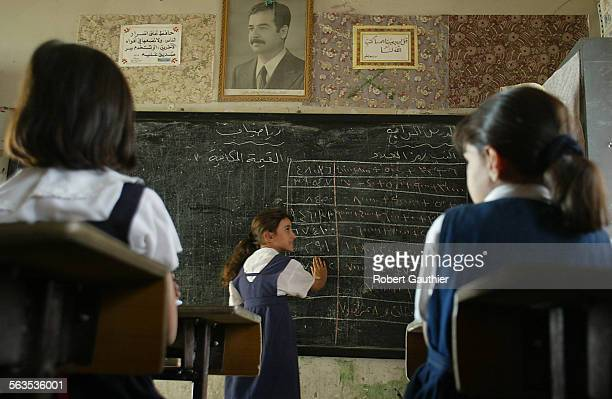 The omnipresent image of Iraqi president Saddam Hussein hangs over a fourth grade math class at Al Mutanaby elementary school in Baghdad Experts...