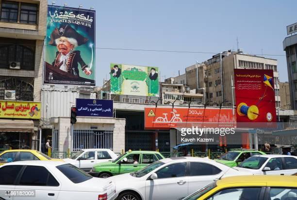 The ongoing traffic in Ferdowsi Square where a banner depicts Queen Elizabeth as a sea pirate with a sword in her hand displayed next to another...