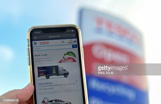 The online shopping website of supermarket Tesco is displayed for a photograph on a smartphone, outside one of the company's stores in Liverpool,...
