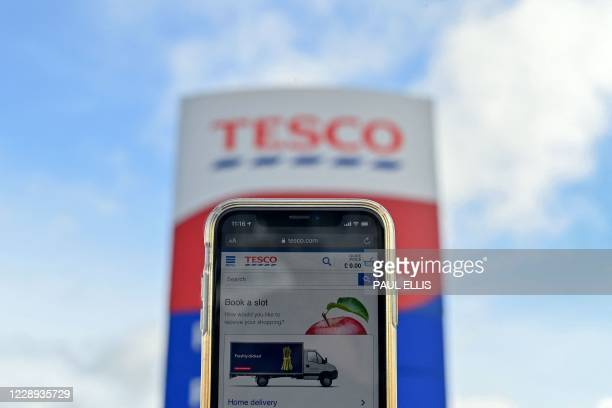 The online shopping website of supermarket Tesco is displayed for a photograph on a smartphone outside one of the company's stores in Liverpool north...