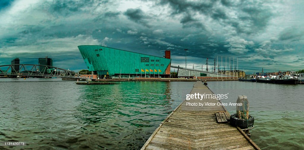 The Oosterdokseiland (Eastern Dock Island), Mr. J.J. van der Veldebrug Bridge and the NEMO Science Museum building from a floating pier in Amsterdam, Netherlands : Foto de stock