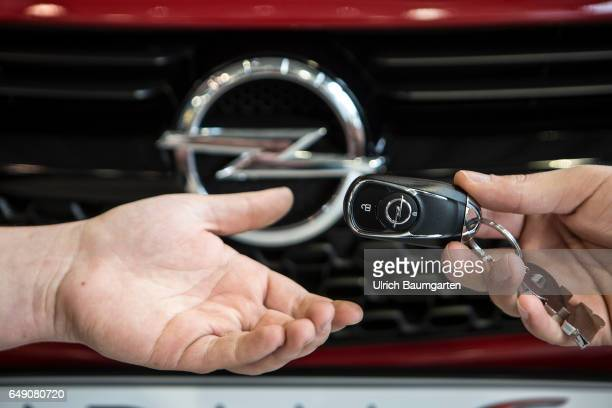 The Opel AG and its future under the new owner PSA Car purchase the symbol photo shows the hand of a passenger car seller with an Opel vehicle key...