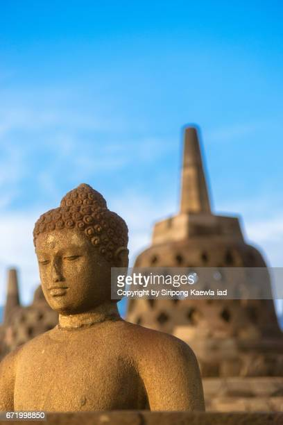 The open buddha statue with stupa in background at the Borobudur, Central Java, Indonesia.