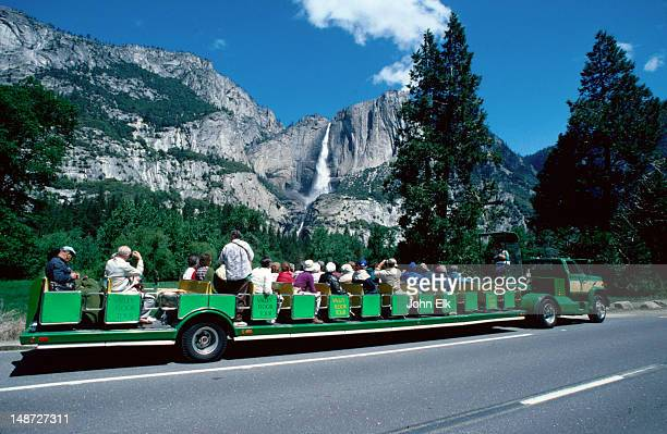 The open tour bus passes the spectacular Yosemite Falls on its tour through the Yosemite Valley- Yosemite National Park, California