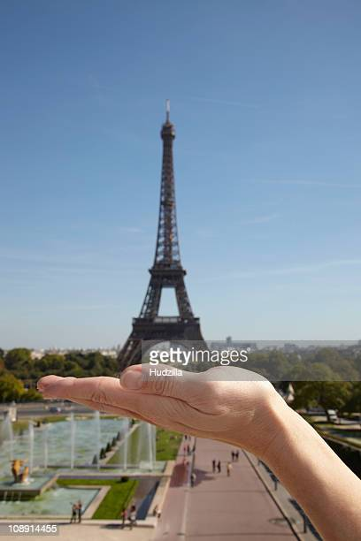 The optical illusion of a woman holding the Eiffel Tower in her hand, focus on hand