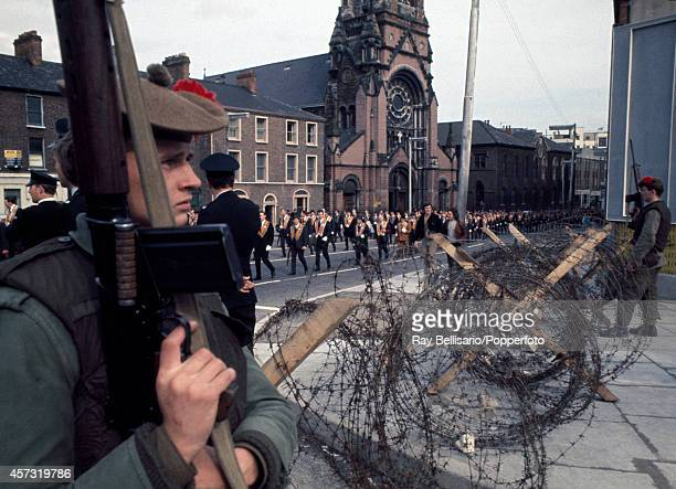 The Orange Order a Protestant fraternal organsation marching in Belfast Northern Ireland watched by British soldiers behind a barbed wire barricade...