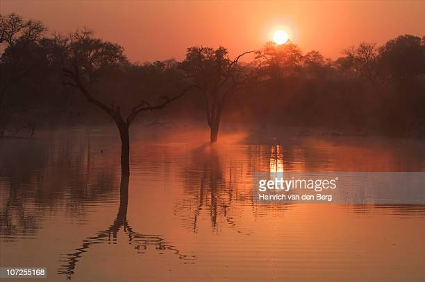 The orange sun setting over the Lower Sabi Dam, South Africa