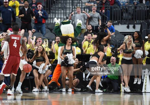The Oregon cheerleaders and band celebrate after Oregon takes the lead during the PAC12 Men's Basketball Tournament game between the Washington State...