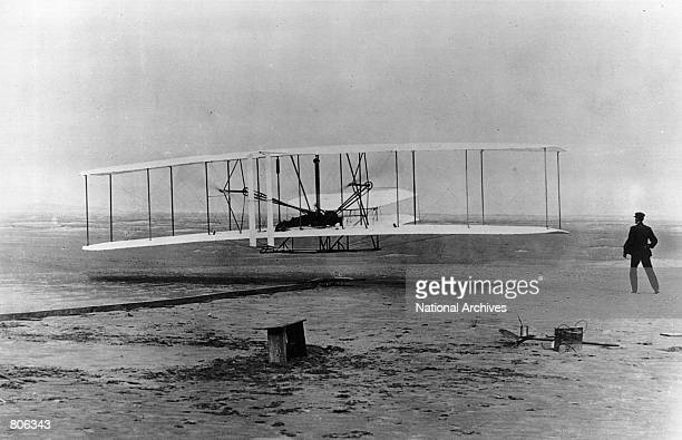 The original Wright Brothers 1903 Aeroplane during it's first flight December 17 1903 in Kitty Hawk North Carolina With Orville Wright at the...