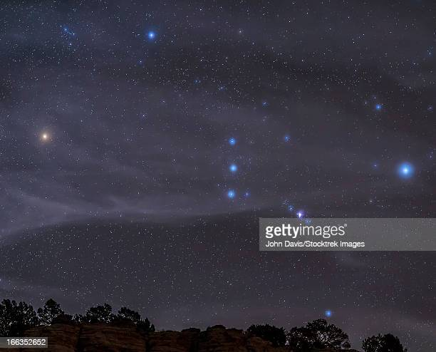 The Orion constellation rises over a hill through high thin clouds near Black Mesa, Oklahoma.