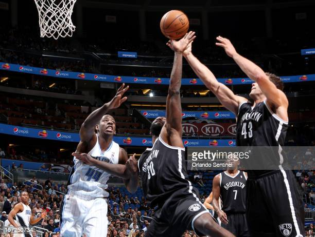 The Orlando Magic's Andrew Nicholson left goes up for a rebound against Reggie Evans and Kris Humphries right of the Brooklyn Nets at the Amway...