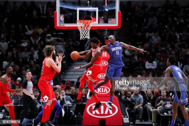 The Orlando Magic's Bismack Biyombo guards the Chicago Bulls' Justin Holiday while he passes the ball to teammate Robin Lopez during the second half...