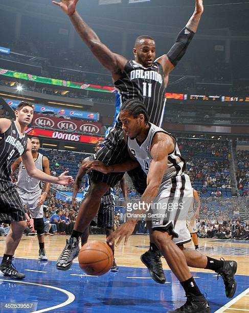 The Orlando Magic's Glen Davis jumps up to block the drive of the San Antonio Spurs' Kawhi Leonard during the first half at the Amway Center in...