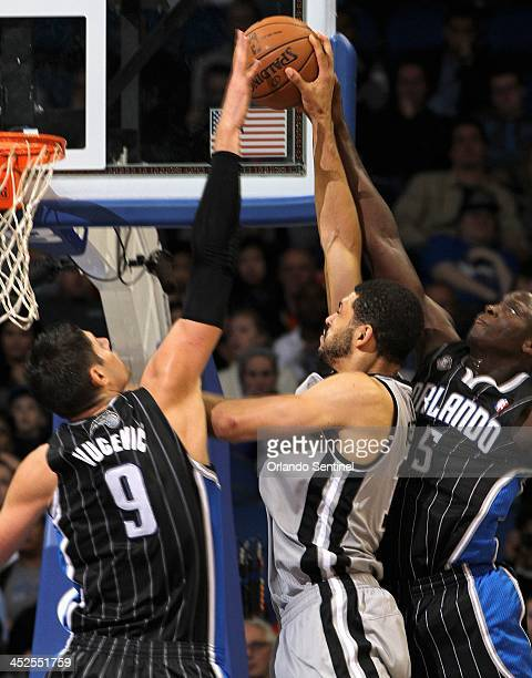 The Orlando Magic's Nikola Vucevic and Victor Oladipo block the shot of the San Antonio Spurs' Jeff Ayres during the second half at the Amway Center...
