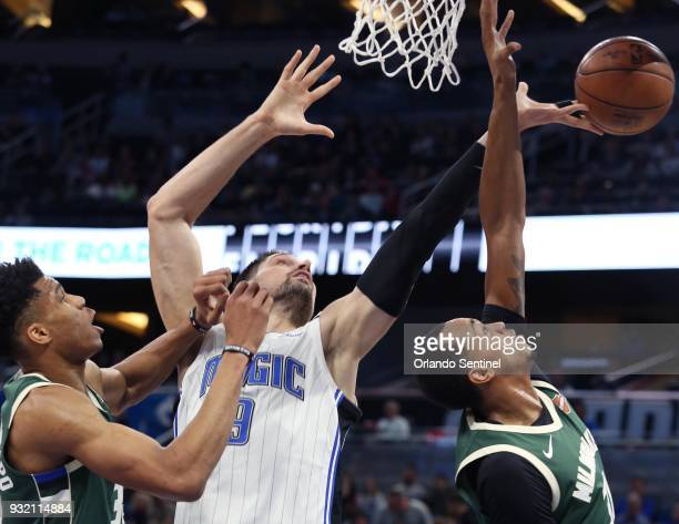 The Orlando Magic's Nikola Vucevic middle battles the Milwaukee Bucks' Giannis Antetokounmpo left and John Henson right at the Amway Center in...