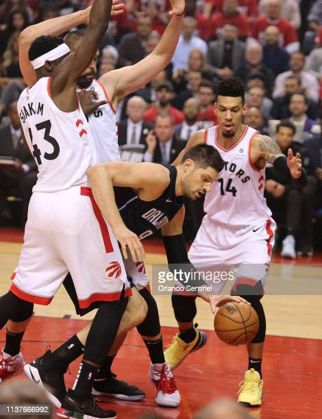The Orlando Magic's Nikola Vucevic middle is swarmed by Toronto Raptors defenders including forward Pascal Sikam and Danny Green during Game 2 in the...
