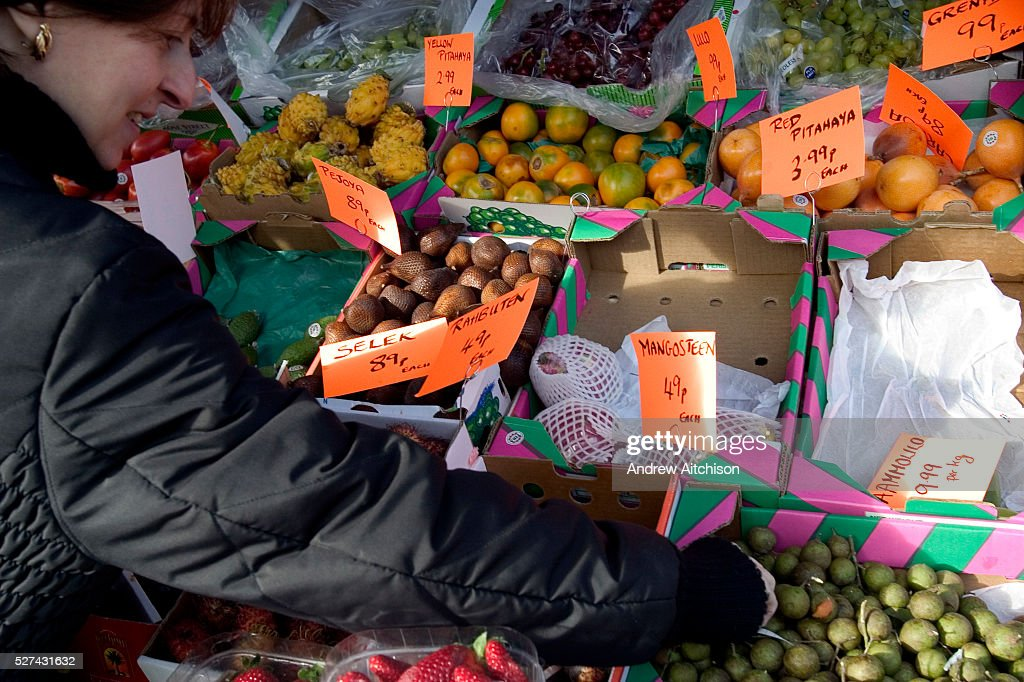 The Orthodox Jewish festival of Tu Bishvat is celebrated as the New Year of trees with a symbolic eating of different varieties of fruit. Here in a Stamford Hill supermarket a woman purchases a selection of different fruits for her family to use in celebration.