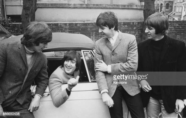 The other members of British rock group the Beatles congratulate John Lennon on passing his driving test 16th February 1965 From left to right George...