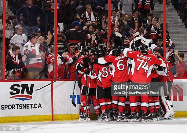 The Ottawa Senators celebrate their overtime goal against the Toronto Maple Leafs in their home opener at Canadian Tire Centre on October 12 2016 in...