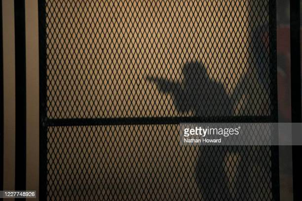 The outline of a federal officer is seen here behind a reinforced version of a fence that protesters dismantled earlier in the week in front of the...