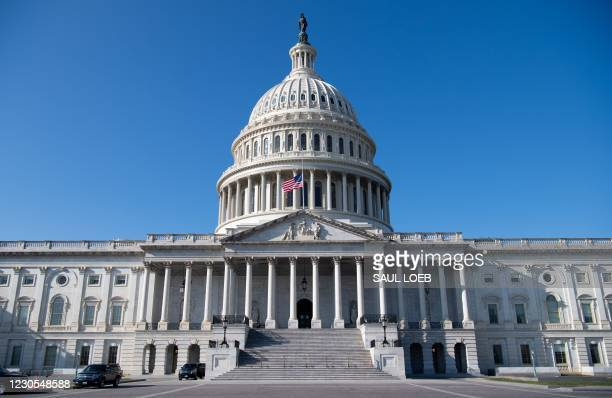 The outside of the US Capitol is seen with a US flag at half-staff in Washington, DC, January 12 ahead of a House vote calling on US Vice President...