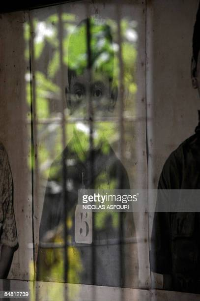 The outside world is reflected in the glass covering a boy's photograph, one of thousands of victims on display at the genocide museum at Tuol Sleng,...