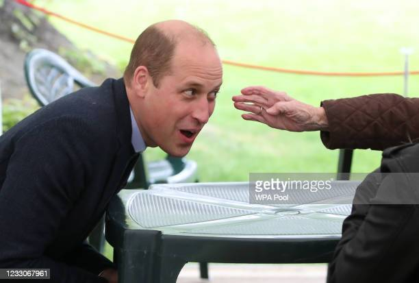 The outstretched hand of resident Betty Magee touches the face of Prince William, Duke of Cambridge during a visit to the Queens Bay Lodge Care Home,...