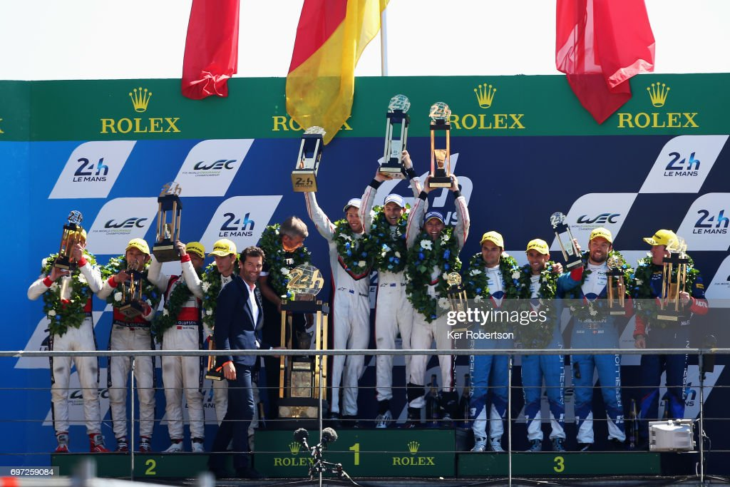 The overall winning The Porsche LMP Team 919 (c) of Earl Bamber, Timo Bernhard and Brendon Hartley celebrate on the podium following the Le Mans 24 Hours race at the Circuit de la Sarthe on June 18, 2017 in Le Mans, France.