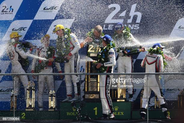 The overall winning The Porsche LMP Team 919 of Earl Bamber Timo Bernhard and Brendon Hartley celebrate on the podium following the Le Mans 24 Hours...
