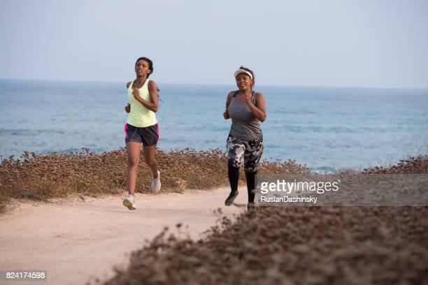 The overweight woman running with a coach together along the sea beach.