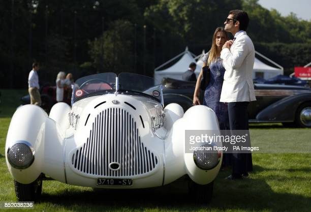 The owner of a 1931 Alfa Romeo 6C 1750 Gran Sport Aprile Spider Corsa adjusts his tie after putting his vehicle on display at the opening of the St...