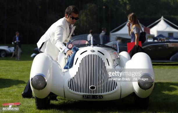 The owner of a 1931 Alfa Romeo 6C 1750 Gran Sport Aprile Spider Corsa polishes his car after putting it on display at the opening of the St...