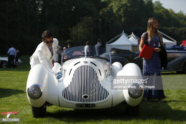 The owner of a 1931 Alfa Romeo 6C 1750 Gran Sport Aprile Spider Corsa gives it a polish while putting the vehicle on display as part of the opening...