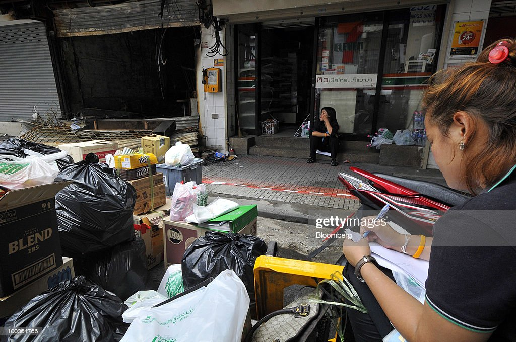 The owner of a convenience store takes inventory of stock left in her looted store in the Siam Square shopping area in Bangkok, Thailand, on Monday, May 24, 2010. Efforts to clean up the city's commercial district gathered pace after the area was torched by rioting anti-government protesters. Photographer: Udo Weitz/Bloomberg via Getty Images