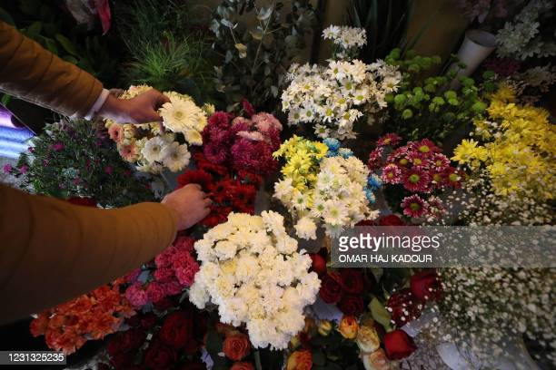 The owner of a flower shop in Idlib prepares a bouquet of fresh flowers grown in a greenhouse in Syria's rebel-held northwestern province, for a...